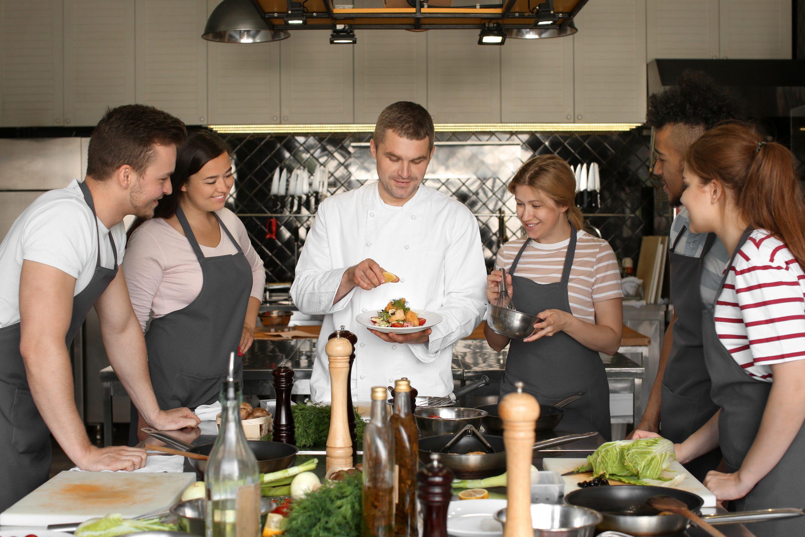idées de sorties Cuisine Chef et groupe de jeunes pendant les cours de cuisine